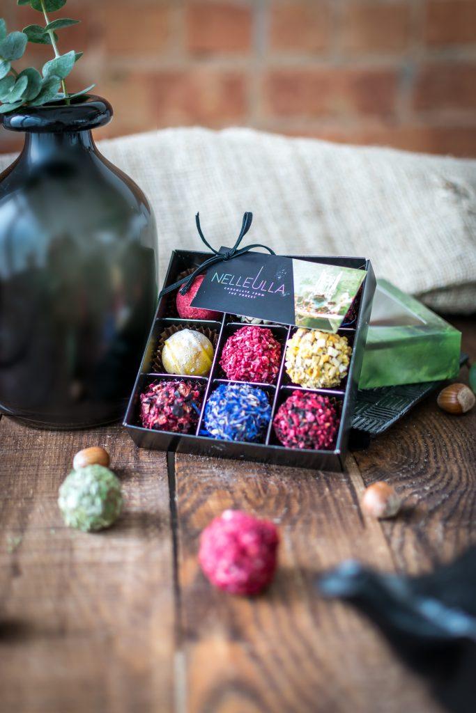 """9-ių vnt. triufelių rinkinys kartoninėje dėžutėje """"FOREST"""" su perregimu langeliu. Tai šokolado meistrų """"Nelleulla"""" rankų darbo kūrinys, nustebinsiantis net 9-iais skirtingais skoniais jungiančiais Belgiško šokolado kokybę bei liofinizuotų uogų grožį."""